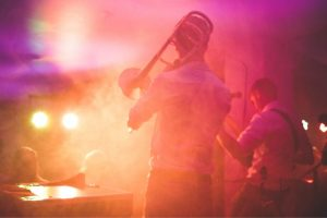 live musician with trombone on stage tinted pink and yellow lighting