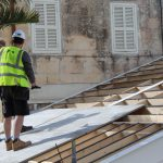 men in hi viz and hard hats install soundproofing on roof