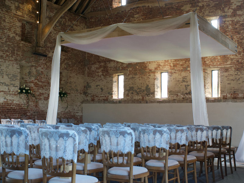 converted barn internal wedding venue with chairs and stage