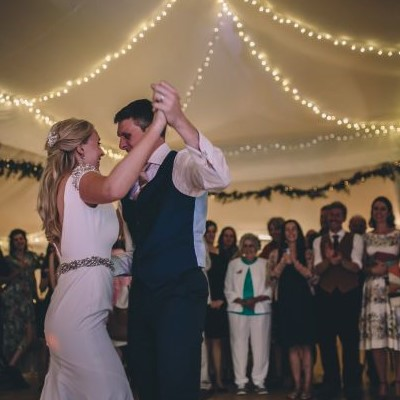 bride and groom dancing in marquee crowd stand in background