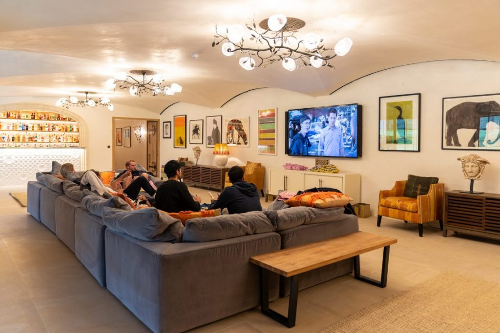 group of people in large sitting room on big grey sofa watching television