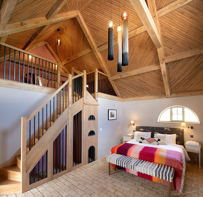 modern bedroom with mezzanine staircase up to bath